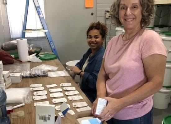 Diana and Kari smile while packing seeds.