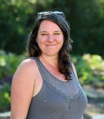 Photo of Jillian Bishop of Urban Tomato smiling in front of her garden.