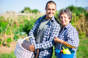 Senior mother and adult son wearing blue checked shirts and carrying garden supplies smile in front of a large vegetable garden.