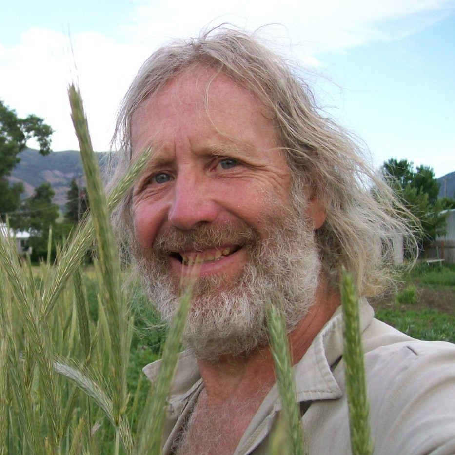 Joseph smiles while standing in a field of landrace rye grass.