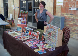 Jillian Bishop smiles behind a table displaying dozens of seed packets for sale at a farmers market.