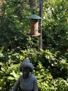 A bird feeder hanging above a garden statue in a green tranquil garden setting